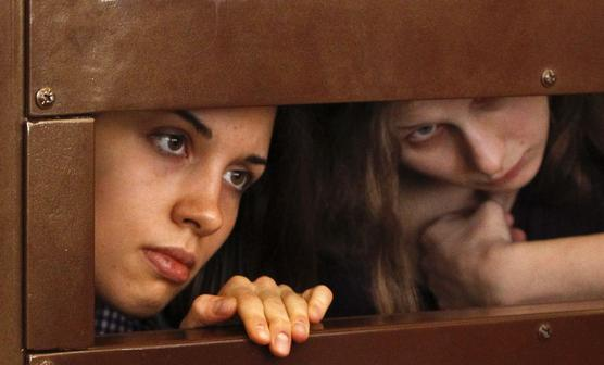 "Tolokonnikova and Alyokhina, members of female punk band ""Pussy Riot"", look out from the defendent's cell in a courtroom in Moscow"